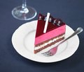Piece of chocolate berry mousse cake on a dark blue background Royalty Free Stock Photo