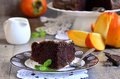 Piece of a chocolate cake with persimmon mint leaf on plate Royalty Free Stock Image