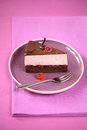 Piece of chocolate cherry mousse cake on a purple plate with silver fork tablecloth Stock Photos