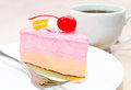 Piece of cream cake with cherry on plate and tea cup Stock Photography