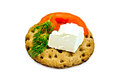 A piece of feta cheese a slice of tomato dill on a round rye crispbread with a light shade on white background Stock Photo