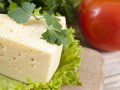 Piece of firm cheese on a table a near greens Royalty Free Stock Images