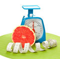 A piece of grapefruit, measure tape and scale Stock Image