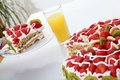 Piece of homemade cake is served with orange juice fruit strawberries and kiwi on the table Stock Images