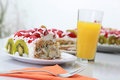 Piece of homemade cake is served with orange juice fruit strawberries and kiwi on the table Stock Photo