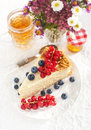 Piece of homemade honey cake with fresh berries decorated blueberries and red currants Stock Photos