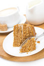 Piece of honey cake on a plate cream and cappuccino cup wooden board close up vertical Stock Photo