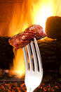 Piece of meat on fork a in front a fire Royalty Free Stock Images