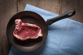 Piece of meat in pan above view on wooden table Royalty Free Stock Photos