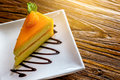 Piece of orange cheese cake in the white plate on the brown bark background Royalty Free Stock Photo