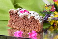 A piece of a tasty homemade chocolate cake on a silver plate with flowers and green cloth as a background. Home cooking Royalty Free Stock Photo