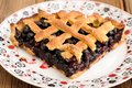 Piece of triangular homemade lattice pie with whole wild blueberries Royalty Free Stock Photo
