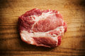 Piece of uncooked marbled steak or meat lying on a wooden counter in a kitchen butchery overhead view with copyspace Stock Photos