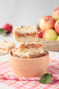 Pieces of apple crumble in bowl a wooden and a bag apples Stock Image