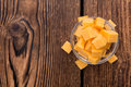 Pieces of cheddar detailed close up shot on rustic wooden background Stock Photos