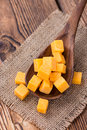 Pieces of cheddar detailed close up shot on rustic wooden background Stock Image