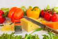 Pieces of cheeses, grated cheese, metal grate, , knife,  tomatoes, peppers and leaves of frillis and arugula Royalty Free Stock Photo