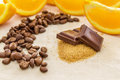 Pieces of chocolate on brown sugar surrounded by orange slices coffe beans Royalty Free Stock Photo