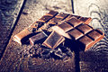 Pieces of chocolate on wooden table Royalty Free Stock Photo