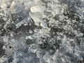 Fragments of beautiful broken ice lay on the ground and sparkle in the sun Royalty Free Stock Photo