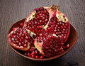 Pieces of pomegranate fruit on wooden table Royalty Free Stock Photos