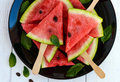Pieces of ripe watermelon on a stick on a black plate on a white Royalty Free Stock Photo