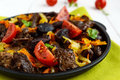 Pieces of roast duck, goose meat, liver, heart with vegetables onion, carrot, tomato, with spices on a round cast-iron frying Royalty Free Stock Photo