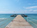 Pier on beach dock looking out over tropical Royalty Free Stock Image