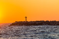 Pier beacon light harbor sunrise color ocean structure for ships navigating channel entry at end of concrete structure at dawn Royalty Free Stock Photos