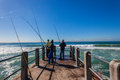 Pier fishermen rods sea blue wellen Stockfotografie