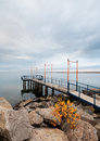 Pier on lake with lanterns the autumn sky and the smooth surface the water Royalty Free Stock Images