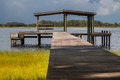 Pier leading to empty boathouse on lake wooden above grass shelter structure with bench water river intracoastal waterway looking Stock Photos
