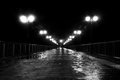 Pier at nights long night with lights reflection black and white Royalty Free Stock Image