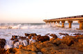 Pier over the sea waves crash under shark rock on port elizabeth s beachfront in south africa Royalty Free Stock Image