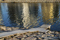 Pier in the river with reflections in the water Royalty Free Stock Photo