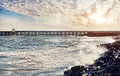 Pier at sunset and sea with waves sky background in puducherry india Royalty Free Stock Image