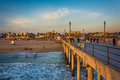The pier and view of the beach at sunset, in Huntington Beach Royalty Free Stock Photo
