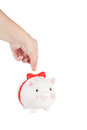 Pig coin box female hand lowers a in a Stock Photo