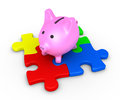 Pig money box on puzzle d top of four pieces Stock Photo