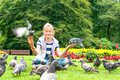 Pigeon Feeding and Balancing on smiling girl`s hands. Summertime