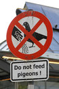 Pigeons feed do not the sign with droppings Royalty Free Stock Photography