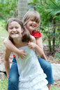 Piggy back little girls playing in a green garden Royalty Free Stock Image