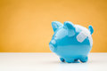 Piggy bank with bandage a blue a standing on a white desk surface an orange background Royalty Free Stock Image