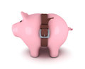 Piggy bank with belt tighten stock image Royalty Free Stock Photography