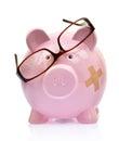 Piggy bank with broken eyeglasses and bandage Royalty Free Stock Image