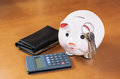 Piggy bank calculator keys and purse on wood table pretty Stock Images