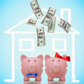Piggy bank couple buying or dreaming of a new home with flying money Royalty Free Stock Image