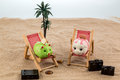 Piggy bank in a deck chair is located symbolic photo for travel and low cost vacation Royalty Free Stock Photos