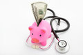 Piggy bank, dollar and stethoscope Royalty Free Stock Image