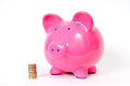 Piggy bank with gbp pink pound icons and notes next to it Stock Photos